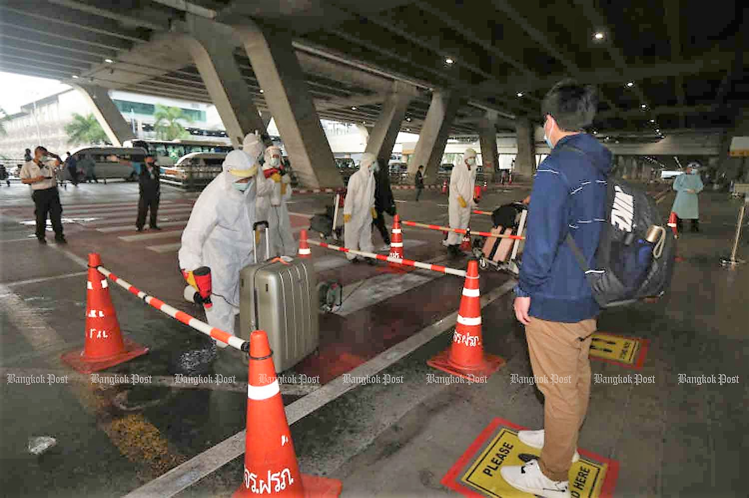 Disease control officials meet passengers arriving at Suvarnabhumi airport and heading to quarantne. (Photo: Varuth Hirunyatheb)