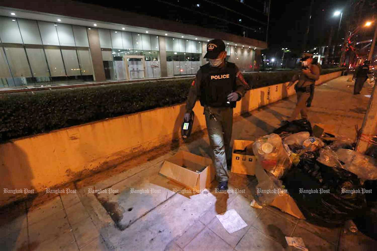 Police examine the protest site outside Siam Commercial Bank headquarters, across from the area where the shooting occurred, in Chatuchak district, Bangkok, after the rally ended on Wednesday night. (Photo: Arnun Chonmahatrakool)