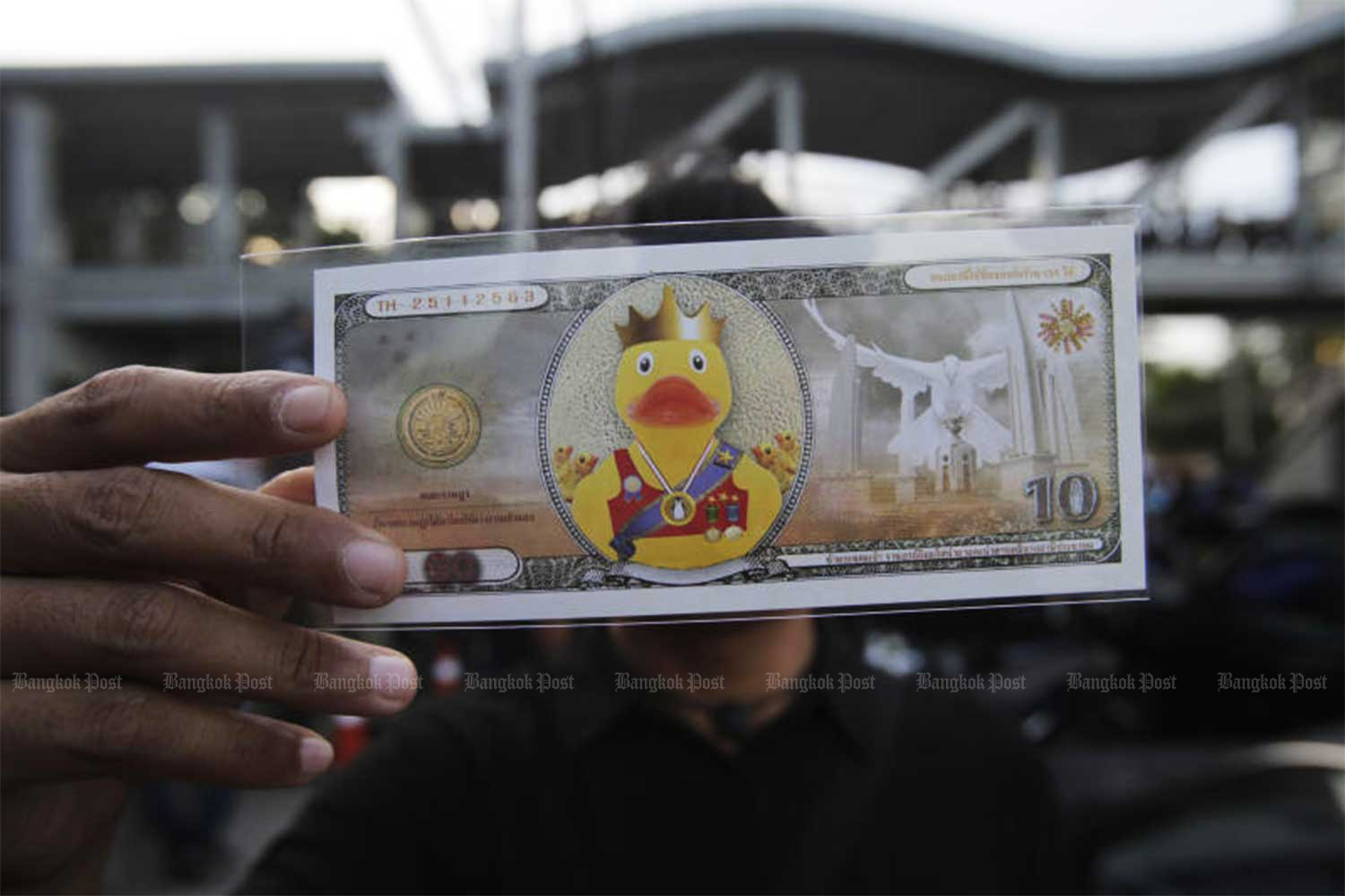 A demonstrator shows a yellow duck coupon for 10 baht handed out to people at the anti-government rally in front of SCB  Park, the headquarters of Siam Commercial Bank, in Bangkok's Chatuchak district on Wednesday evening.(Photo by  Arnun Chonmahatrakool)