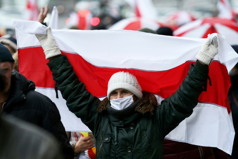 A woman carrying the white-red-white flag used by the anti-Lukashenko movement on Nov 23.
