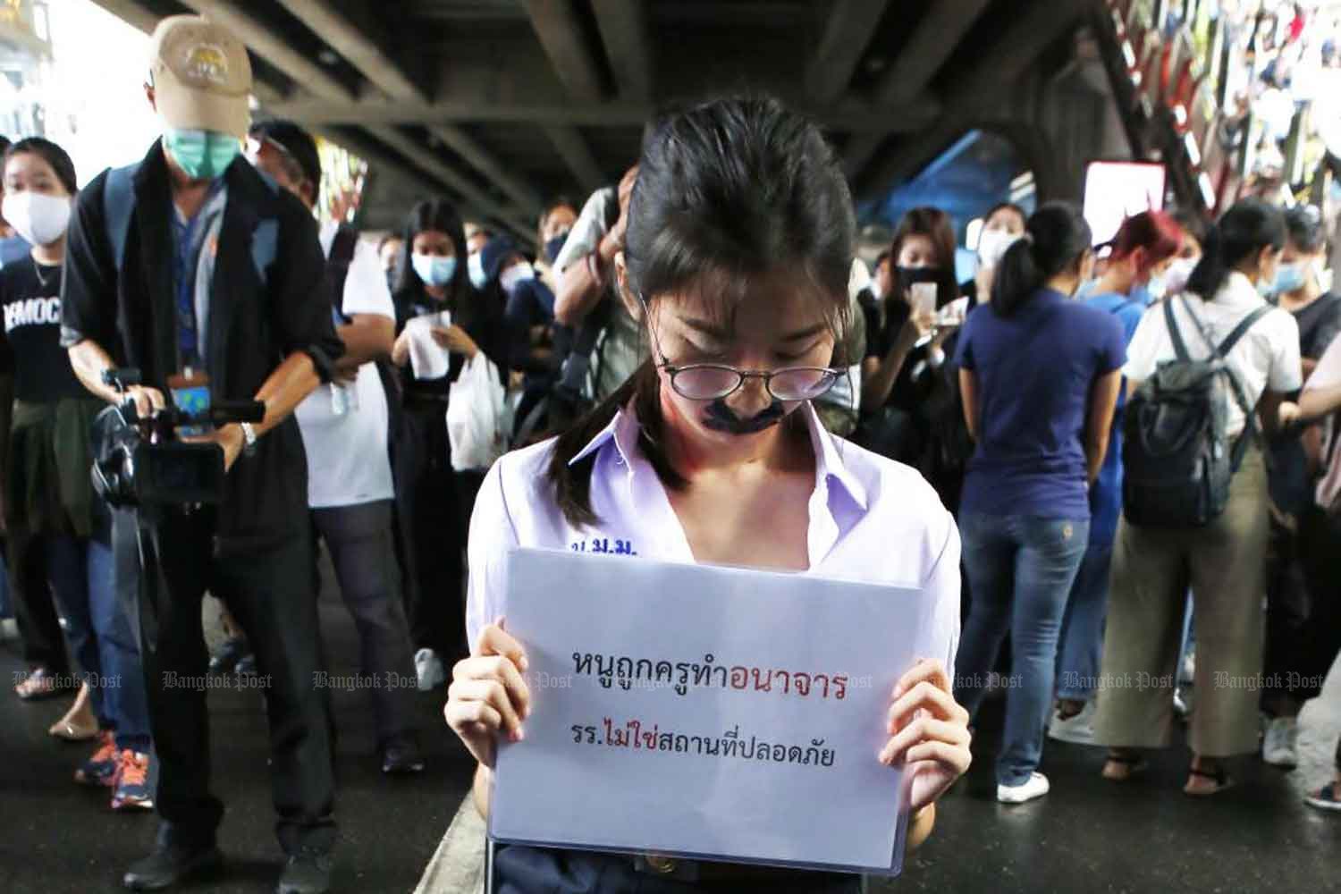 Nalinrat Tuthubthim holds a placard saying: 'A Teacher Committed Sexual Abuse Against Me. Schools Are Not Safe' during a recent protest. (Photo by Apichit Jinakul)