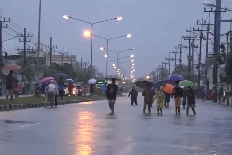 Pedestrians cross a flooded street in Muang district of Songkhla following heavy rain on Monday night. (Photo: Assawin Pakkawan)