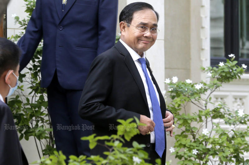 Prime Minister Prayut Chan-o-cha smiles to reporters as he leaves a meeting on Covid-19 at Government House on Wednesday. (Photo: Pornprom Satrabhaya)
