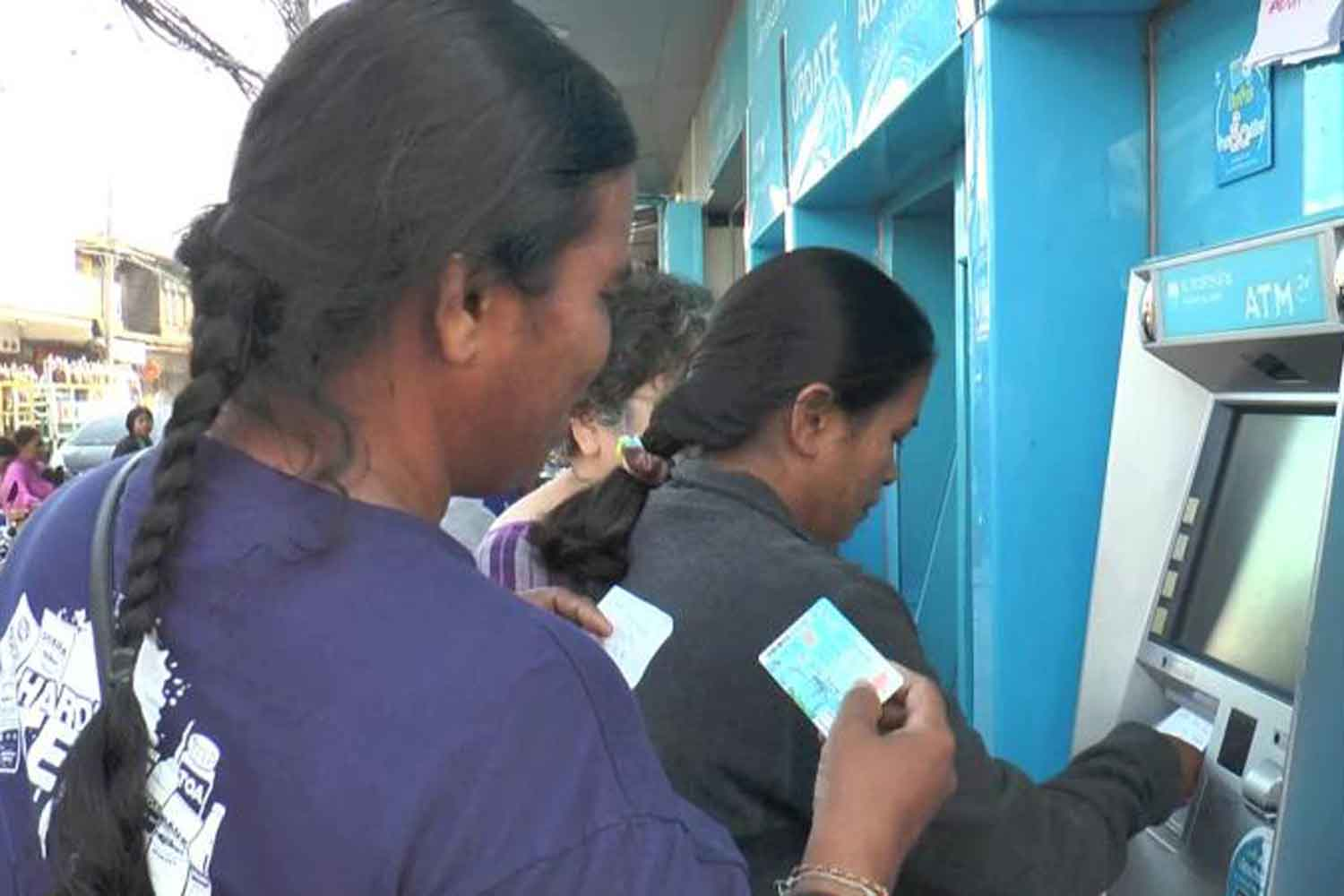 Welfare card holders are withdrawing money from an ATM in Buri Ram province last year. (Photo: Surachai Piraksa)