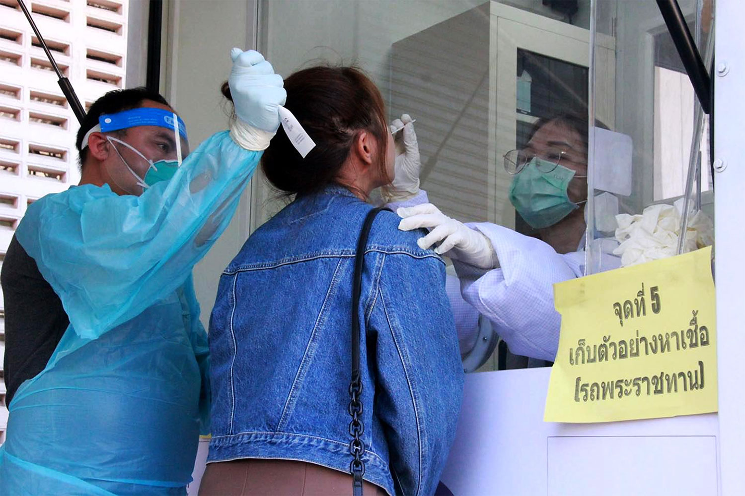A woman receives a Covid-19 swab test at a mobile test site in Muang district, Chiang Rai on Saturday. The province provided free tests for at-risk people who attended the same concert as an infected person who illegally entered the kingdom through natural channels.