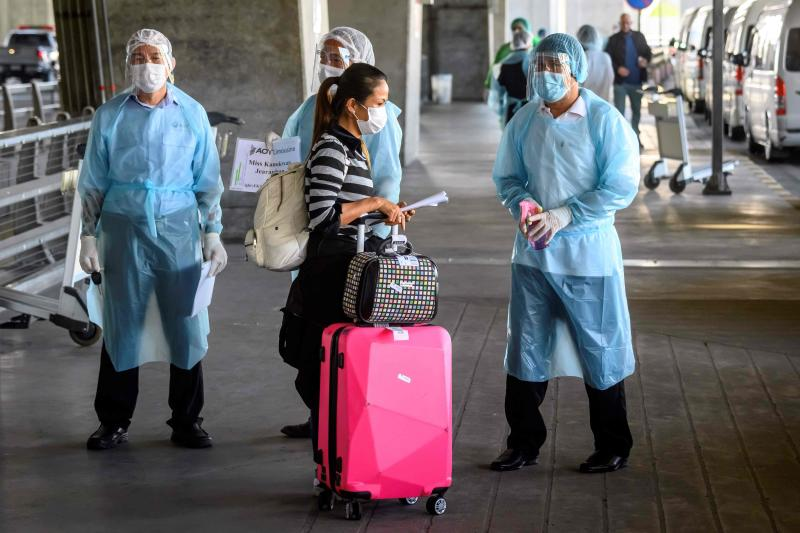 FILE PHOTO: Employees wearing personal protective equipment (PPE) meet an arriving international flight passenger before her transfer to a hotel for the compulsory 14-day Alternative State Quarantine (ASQ), to prevent the spread of the Covid-19 coronavirus, at Suvarnabhumi Airport in Samut Prakan on Nov 16, 2020. (AFP)