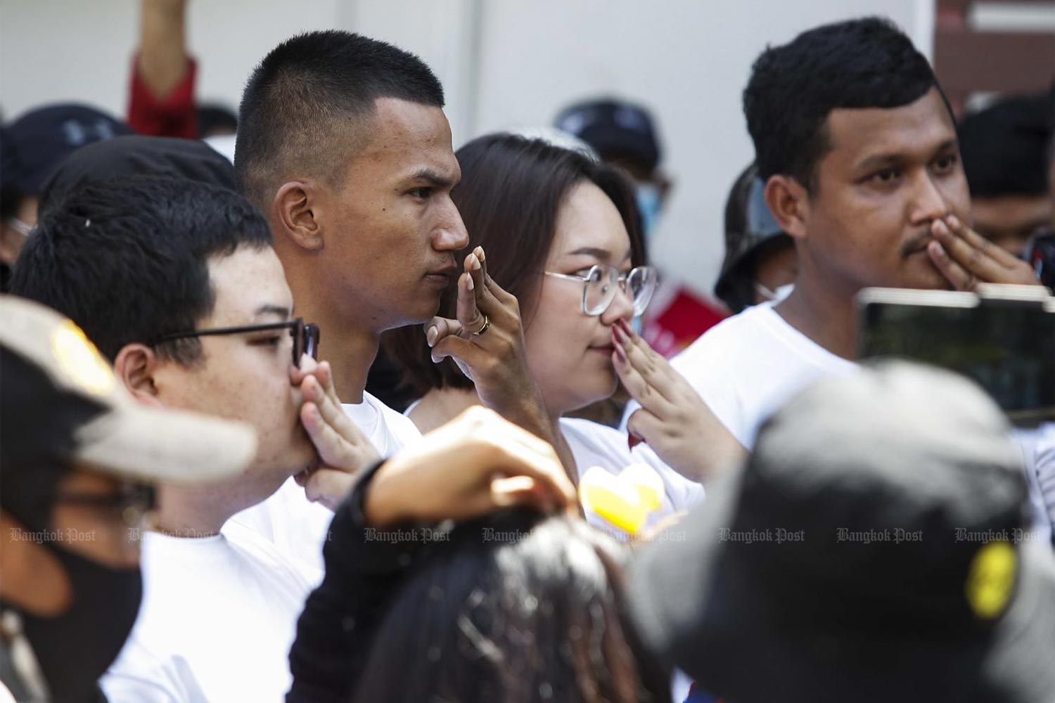 Protest leaders, Parit Chiwarak, left, Panupong Jadnok, Panusaya Sithijirawattanakul, and Chinnawat Chankrachang, right, cover their mouths to protest the violation of their freedom of expression as they report to Nonthaburi police station to hear lese majeste charges.(Photo by Pattarapong Chatpattarasill)