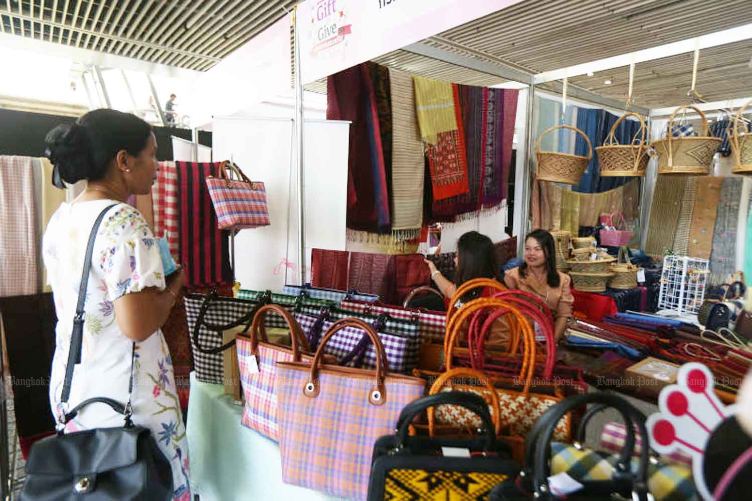 A visitor to a trade fair looks at bags, at MBK shopping centre in Bangkok on Wednesday,  when 18 new Covid-19 cases were recorded. (Photo: Varuth Hirunyatheb)