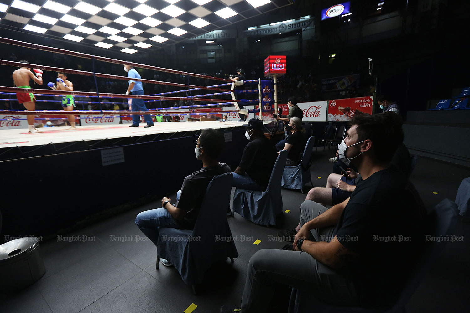 Safer boxing: Staff use disinfectant sprays to clean the arena at the Ratchadamnoen boxing ring in Bangkok yesterday. Spectators watching the match are also spaced apart in keeping with social distancing rules. Public health safety measures have been stepped up in recent days after the resurgence of Covid-19 in some provinces triggered by imported infections through Chiang Rai. (Photos by Varuth Hirunyatheb)