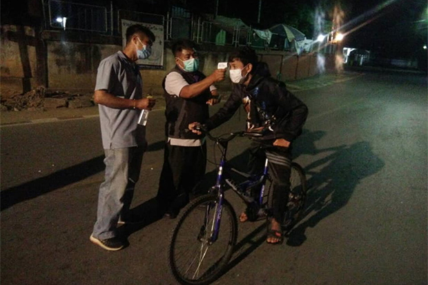 Village defence volunteers check the temperature of a cyclist at Ban Phang Kham in Mae Sai district on Thursday night, as authorities in Chiang Rai step up measures against Covid-19. (Photo: Mae Sai district office Facebook)