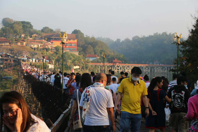 Visitors throng Saphan Mon, the country's longest wooden bridge, in Sangkhla Buri district of Kanchanaburi on Saturday. (Photo by Piyarat Chongcharoen)