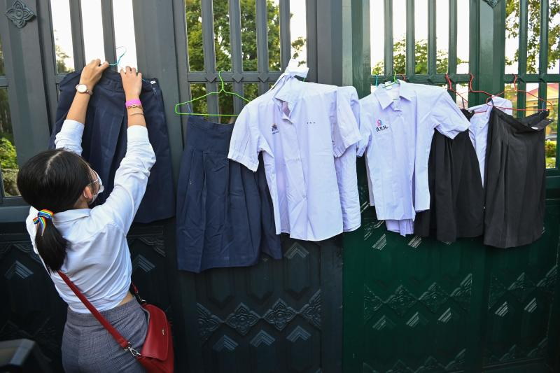 A protester hangs up school uniforms on the gate of the Ministry of Education during a