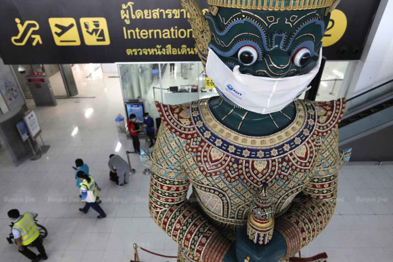 The 'yak' statue at Suvarnabhumi airport wears a face mask as part of a campaign to remind people to continue wearing masks and observe social distancing to prevent transmission of Covid-19. (Photo: Wichan Charoenkiatpakul)