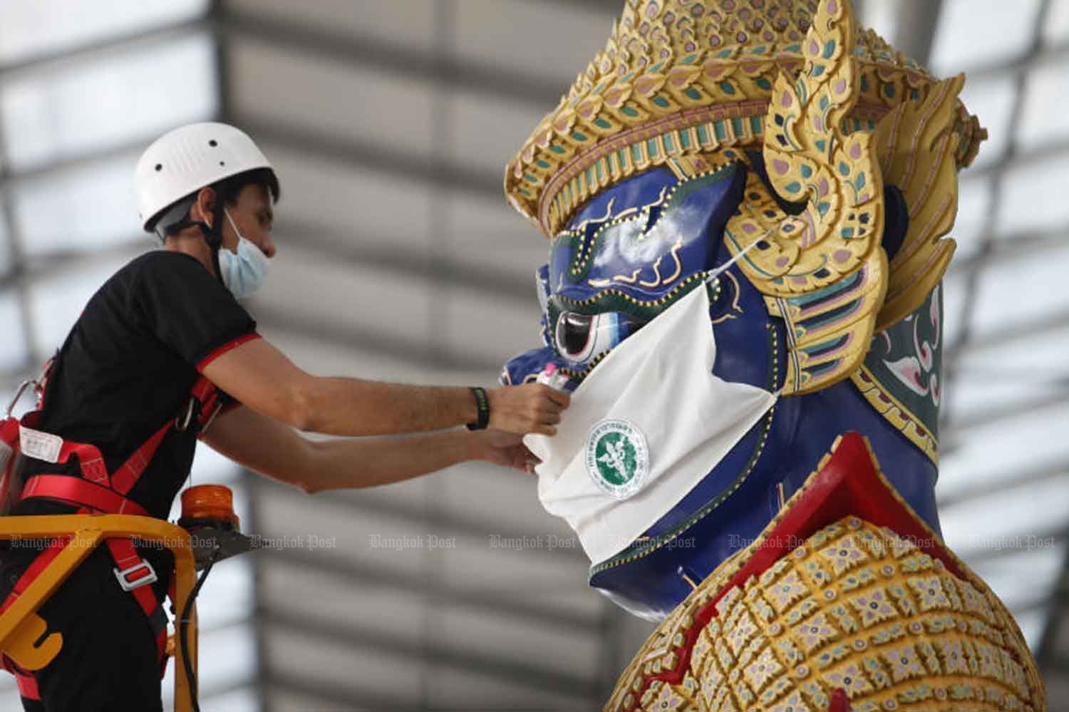 A worker puts a mask on the statue of a guardian demon in the passenger terminal at Suvarnabhumi airport on Monday, part of the campaign to get people to wear masks to contain the spread of Covid-19. (Photo: Wichan Charoenkiatpakul)