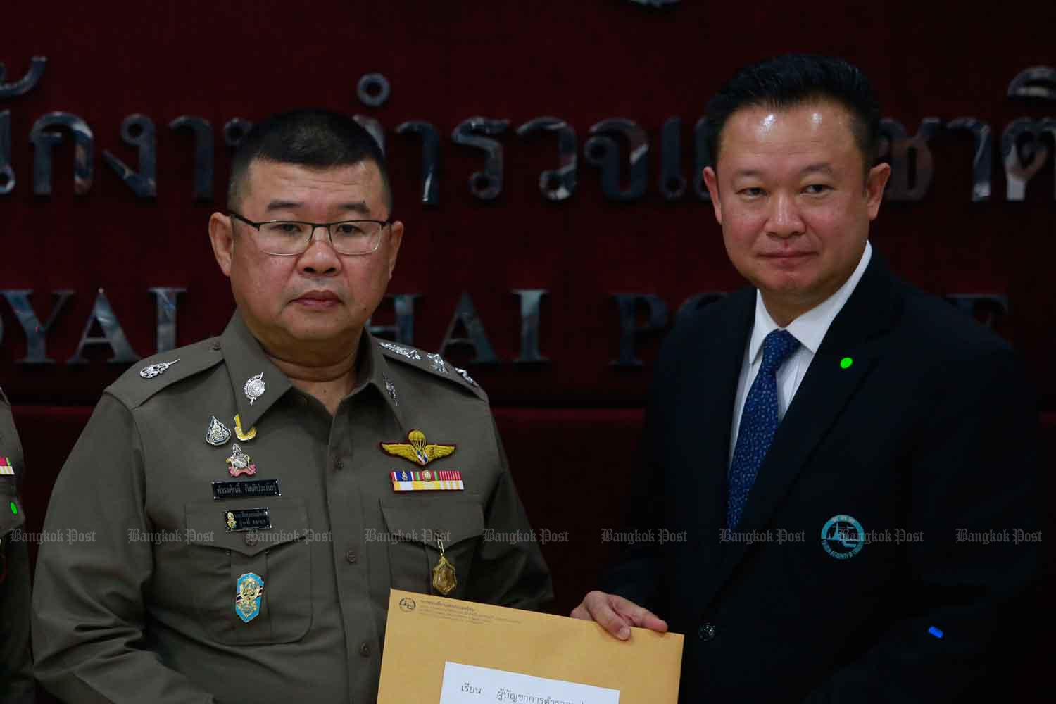 Tourism Authority of Thailand governor Yuthasak Supasorn, right, files a complaint with deputy national police chief Pol Gen Damrongsak Kittiprapat at the Royal Thai Police Office in Bangkok on Wednesday. (Photo: Arnun Chonmahatrakool)