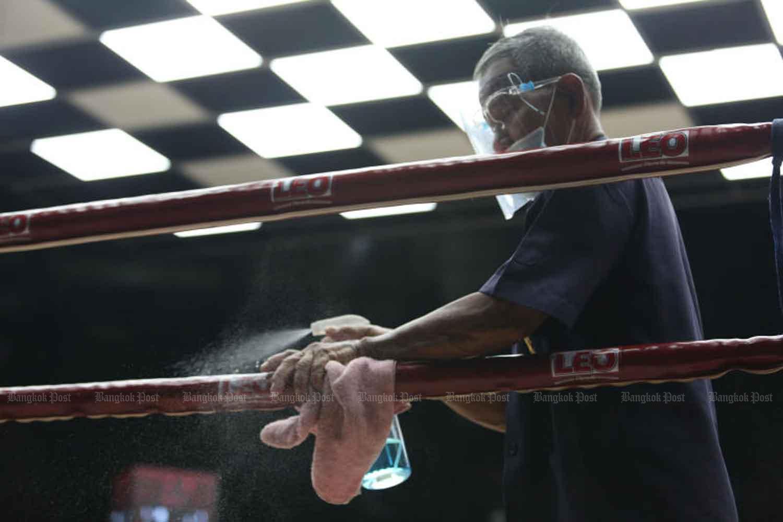 A worker disinfects the ropes of the ring at Rajadamnern boxing stadium in Pomprap Satrupai district, Bangkok. (Photo: Varuth Hirunyatheb)