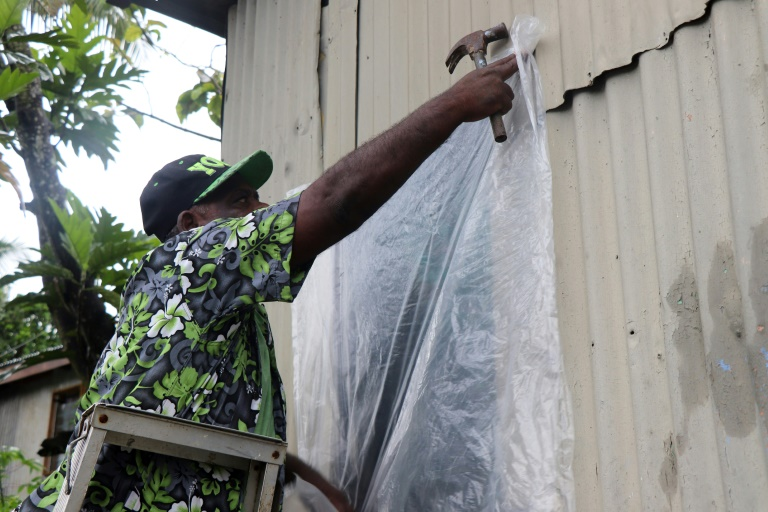 A resident of Fiji's capital Suva prepares his home for the arrival of super Cyclone Yasa.