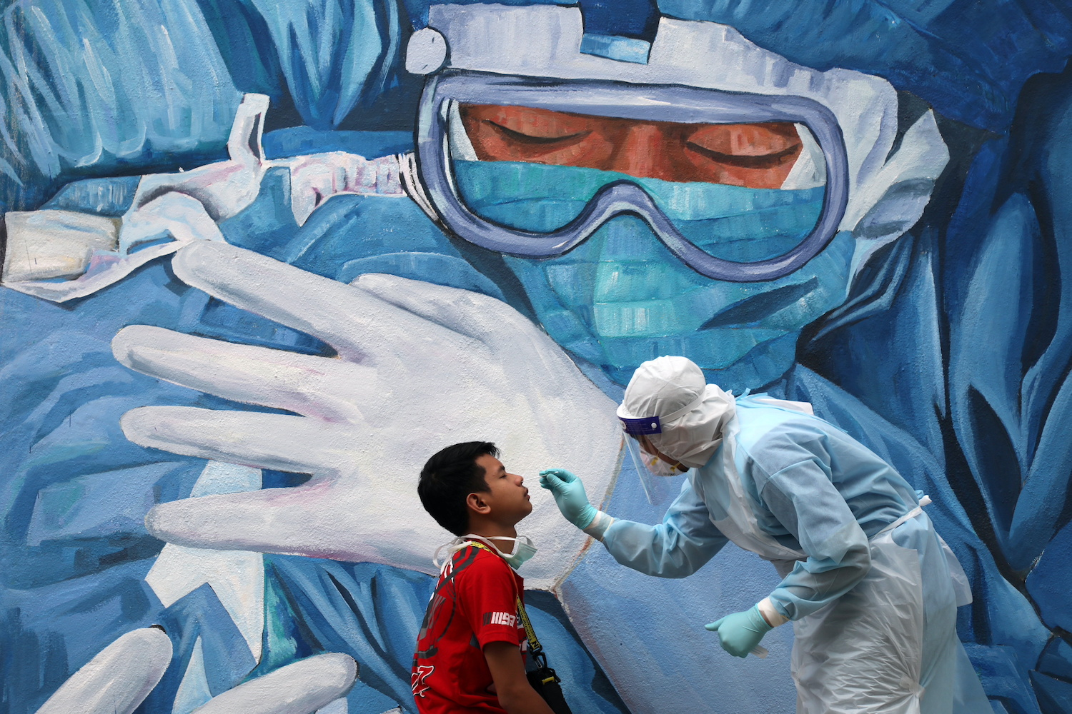 A doctor collects a swab sample outside Clinic Ajwa in Shah Alam, Malaysia. (Reuters Photo)
