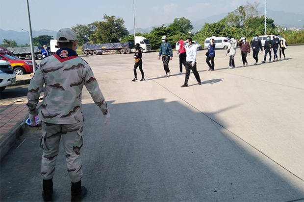 A security official watches 10 Thais returning from Tachilek to Mae Sai district of Chiang Rai through the checkpoint at the second Thai-Myanmar Friendship Bridge on Dec 7, 2020. (Photo fromMai Sai district office Facebook)