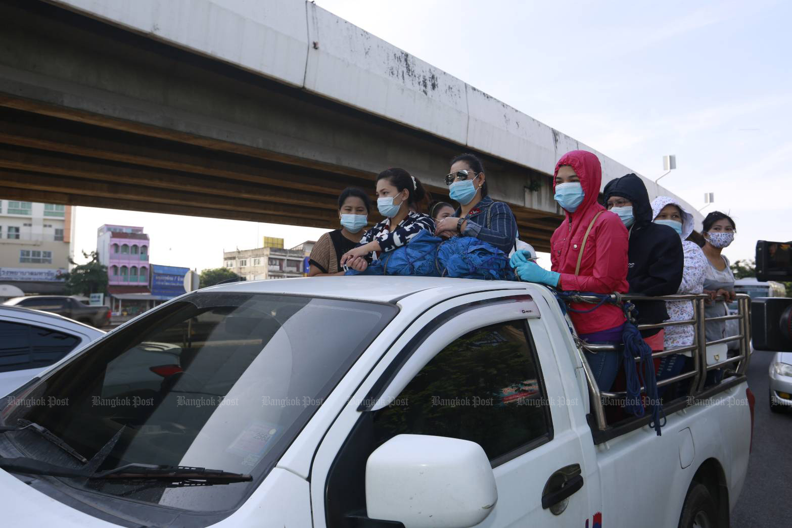 Workers ride on a pickup truck in Muang district of Samut Sakhon on Sunday after the city was sealed to prevent the spread of the coronavirus. (Photo by Arnun Chonmahatrakool)