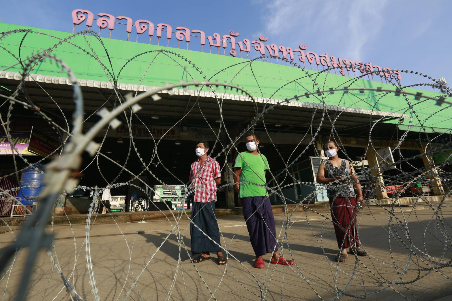 Migrant workers from Myanmar stand behind razor wire blocking the entrance to the Central Shrimp Market linked to an outbreak of Covid-19, in Muang district of Samut Sakhon on Sunday. (Photo by Arnun Chonmahatrakool)