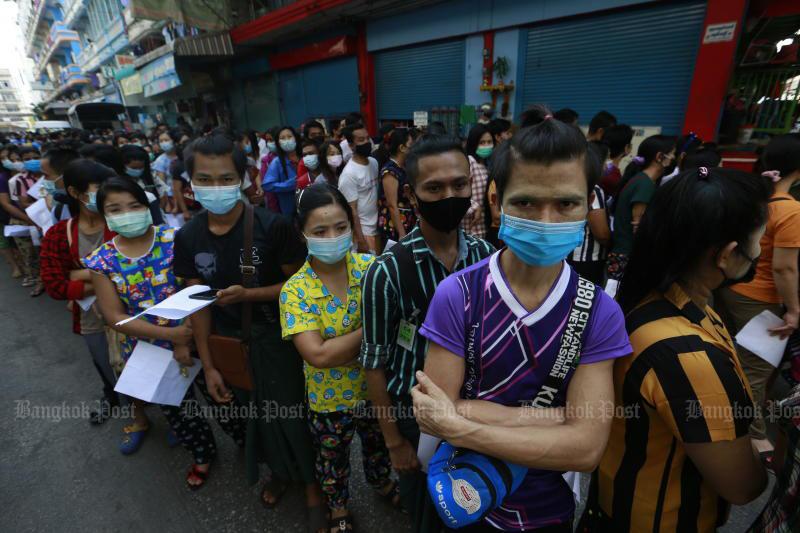Myanmar workers queue for coronavirus tests in Muang district of Samut Sakhon on Sunday. (Photo: Arnun Chonmahatrakool)