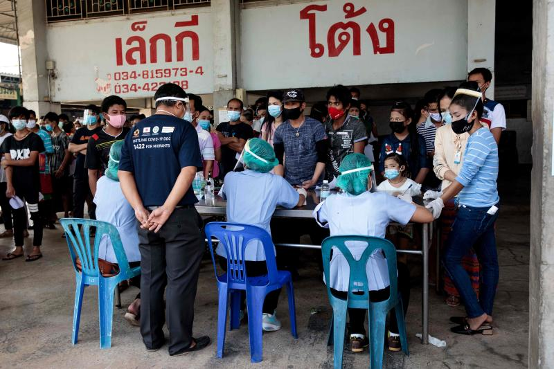 People queue to get tested for the Covid-19 coronavirus at a seafood market in Samut Sakhon on Saturday after cases of local infections were detected and linked to a vendor at the market. (AFP file photo)
