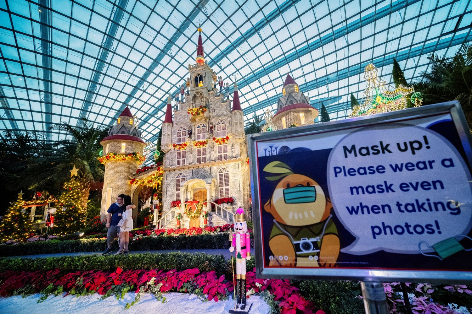 A sign reminds people to wear their protective masks due to the ongoing coronavirus disease outbreak, during the Poinsettia Wishes floral display, as part of the Christmas celebrations at Gardens by the Bay in Singapore on Sunday. (Reuters photo)