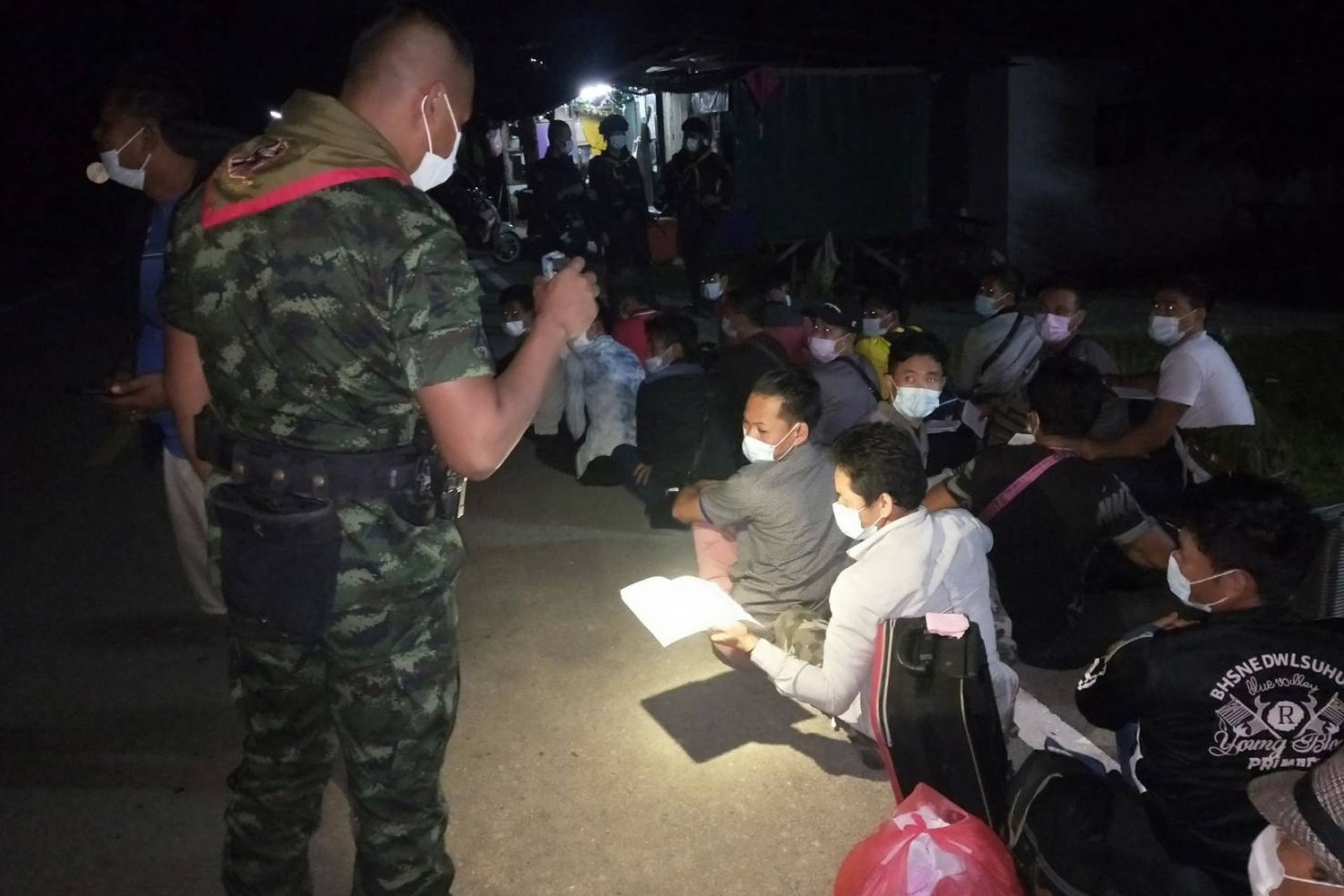 A soldier checks identification papers of a Lao national, one of 32 held in custody for illegal entry, after they entered Thailand in the early hours of Tuesday. (Photo supplied by Waedao Harai)