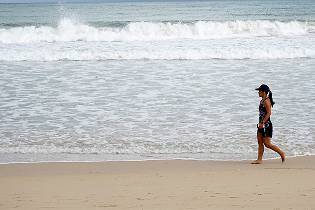 A tourist walks on a beach in Phuket on June 9, 2020 as Phuket attempts to jumpstart its economy after months of lockdown. (Photo by Achadtaya Chuenniran)