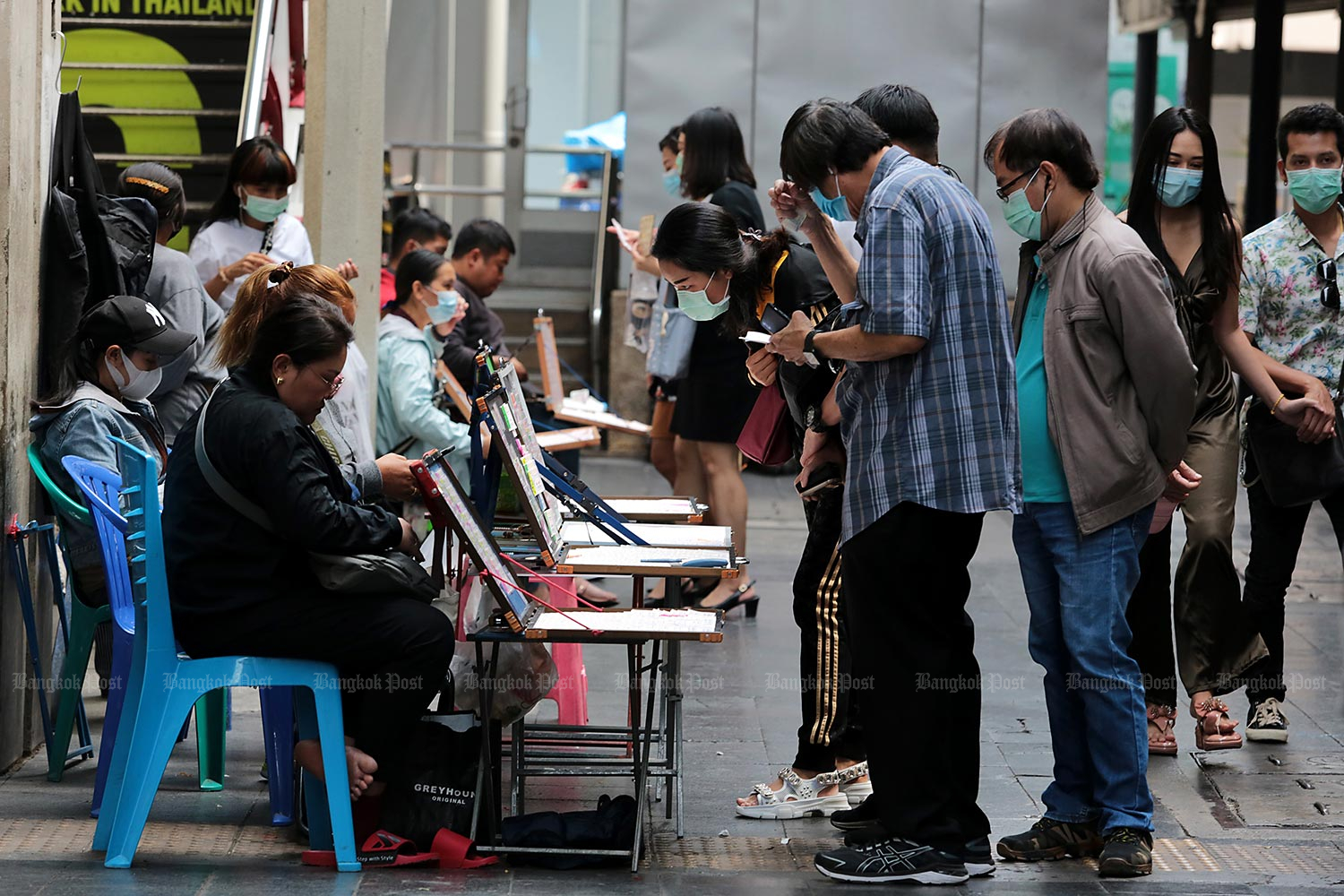 Looking for luck: People look at lottery tickets at Pathumwan intersection on Wednesday. The Government Lottery Office announced the Dec 30 draw will go ahead as usual despite the resurgence of Covid-19 in many provinces, including Bangkok. (Photo by Chanat Katanyu)