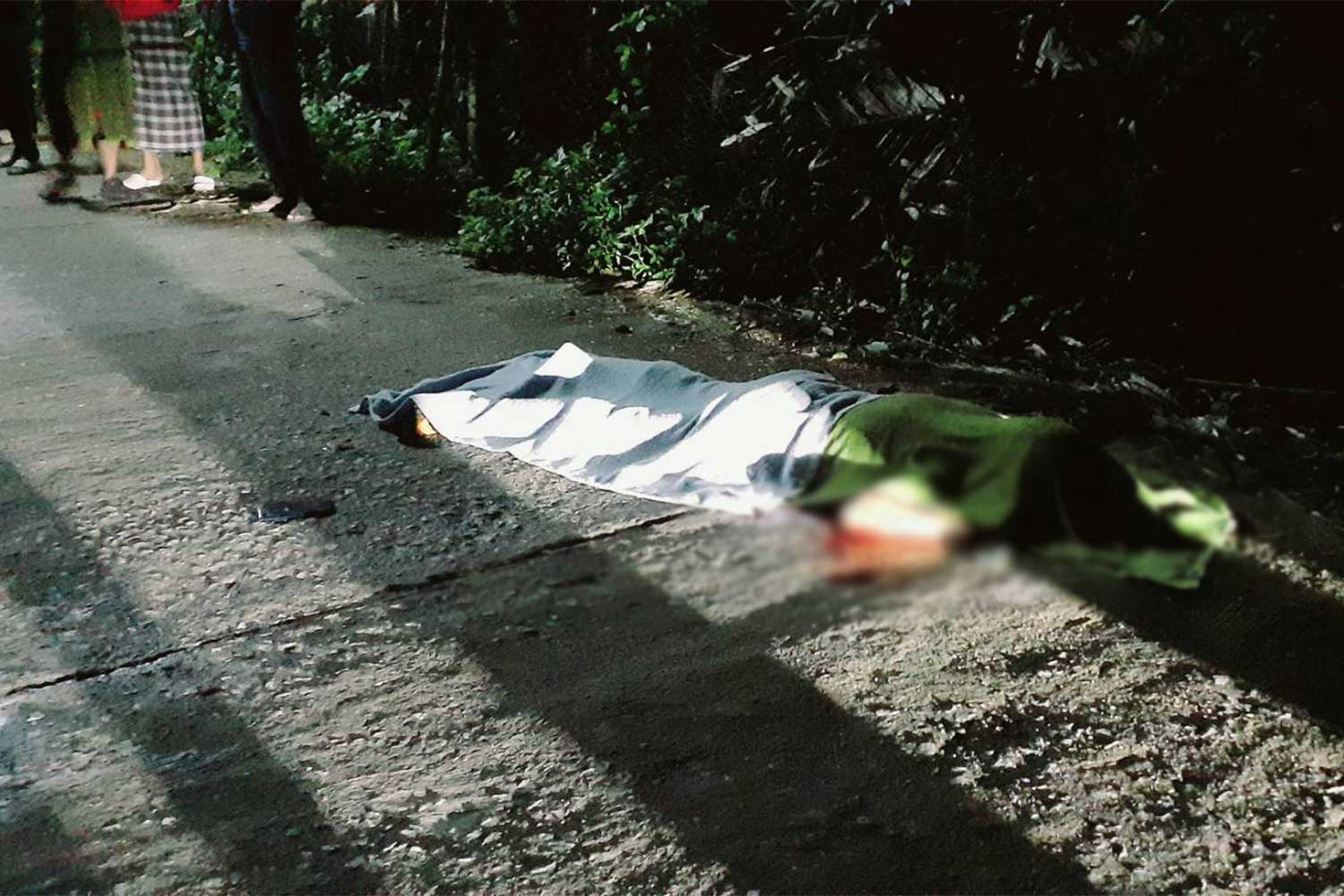 The body of the slain 26-year-old man lies on the road in tambon Torbon of Sai Buri district, Pattani, on Thursday morning. (Photo: Abdullah Benjakat)