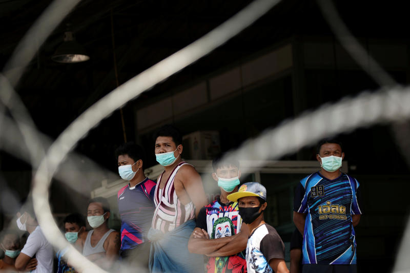 Migrant workers stand in front of the closed Central Shrimp Market in Muang district of Samut Sakhon province on Sunday. (Reuters photo)