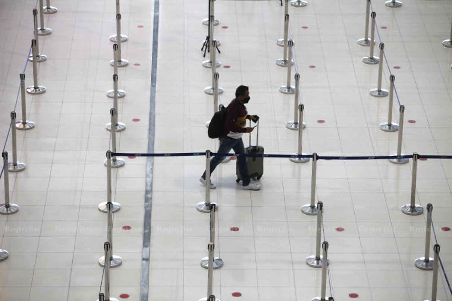 A passenger is checking in for a flight at Suvarnabhumi airport in Samut Prakan province mid this month. (Photo by Wichan Charoenkiatpakul)
