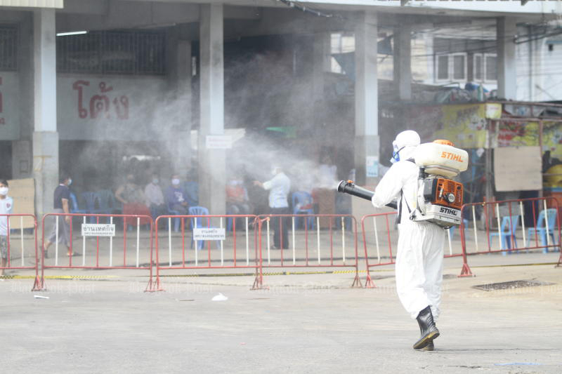 A health worker sprays disinfectant at the Central Shrimp Market in Muang district of Samut Sakhon province on Thursday, to clear the area for a field hospital set up there on Friday. (Photo: Arnun Chonmahatrakool)