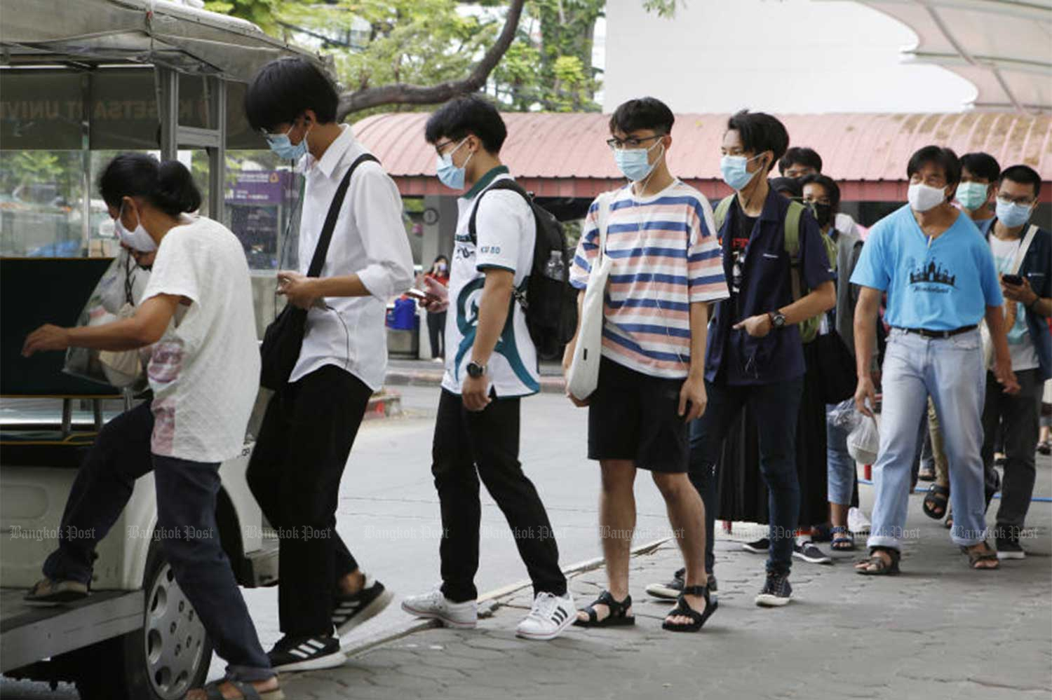People wear face masks as they are about to board a vehicle at Kasetsart University in Bangkok on Friday. (Photo by Apichit Jinakul)
