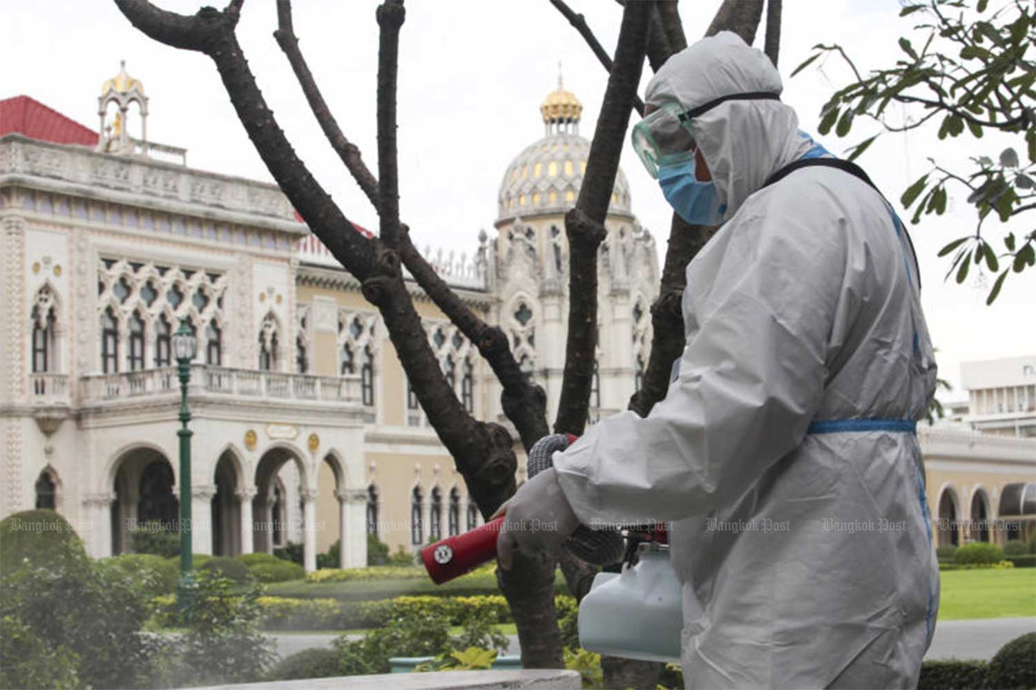 A worker prepares to spray the compound of Government House on Saturday to prevent the spread of Covid-19. Six people in the complex tested positive in a rapid test this week, but a follow-up swab test showed it was a false positive. Nevertheless, authorities want to ensure the area is safe. (Photo by Apichart Jinakul)