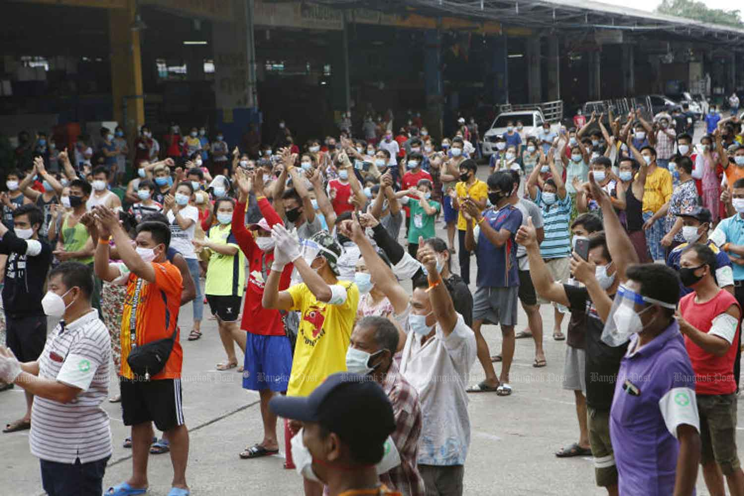 Migrant workers and migrant health volunteers clap their hands to welcome Public Health Minister Anutin Charnvirakul, who inspected measures to handle the Covid-19 outbreak at the Central Shrimp Market in Samut Sakhon province on Sunday. The market and Sri Muang dormitory are designated as off-limits areas for disease control. (Photo: Apichit Jinakul)