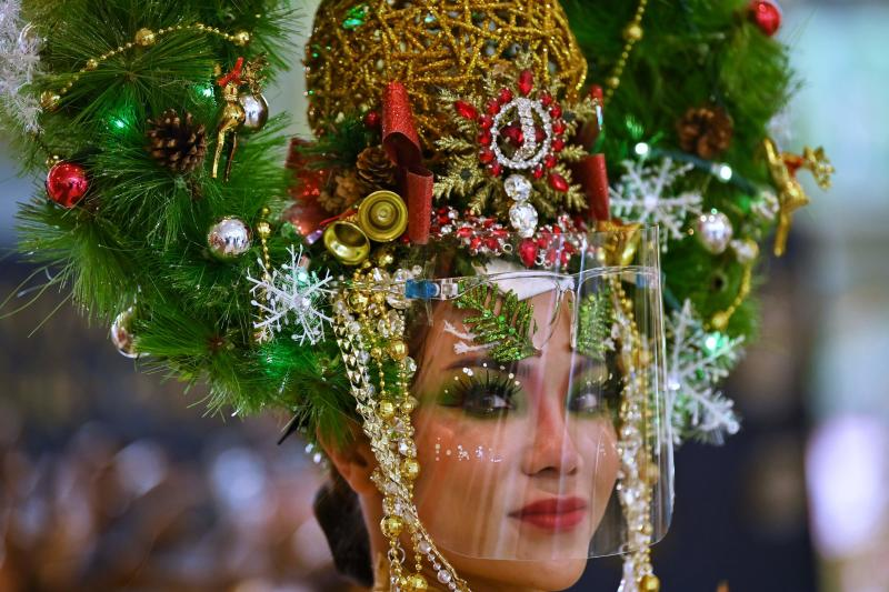 A model dressed as a Christmas tree and wearing a face shield poses for photos in a shopping mall in Bangkok on Dec 24, 2020. The Bank of Thailand has given small- and medium-sized enterprises a late Christmas present. (AFP photo)