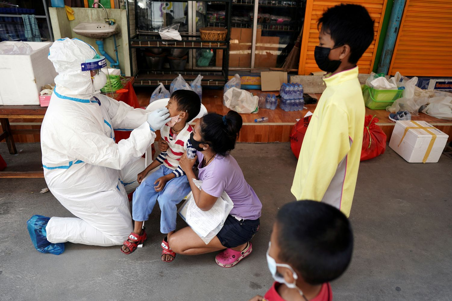 A healthcare worker takes a nasal swab sample of a child for a Covid-19 test at a migrant community in Samut Sakhon province on Dec 20. (Reuters photo)