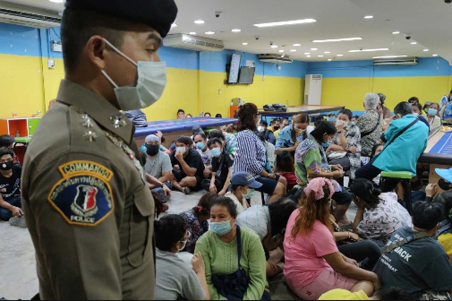 Gamblers, not all wearing face masks, caught during a raid in Bangkok's Laksi district on Monday night. A total of 94 people, Thais and foreign nationals, were arrested. (Photo: Central Investigation Bureau)