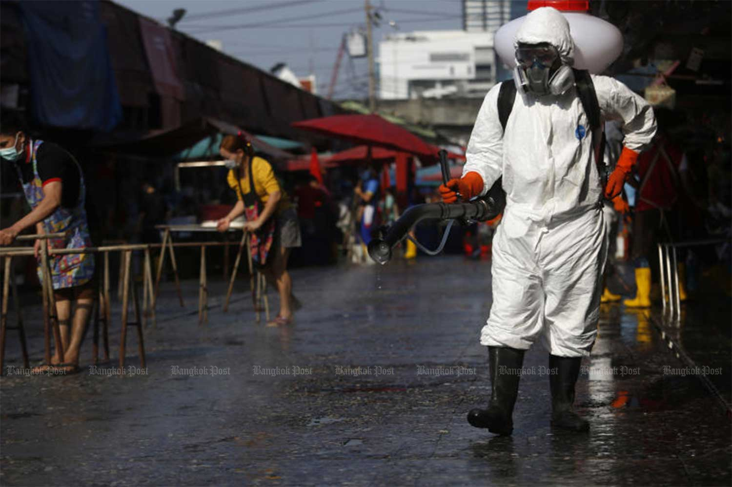 A health official sprays disinfectant at Klong Toey market in Bangkok on Tuesday.(Photo by Wichan Charoenkiatpakul)