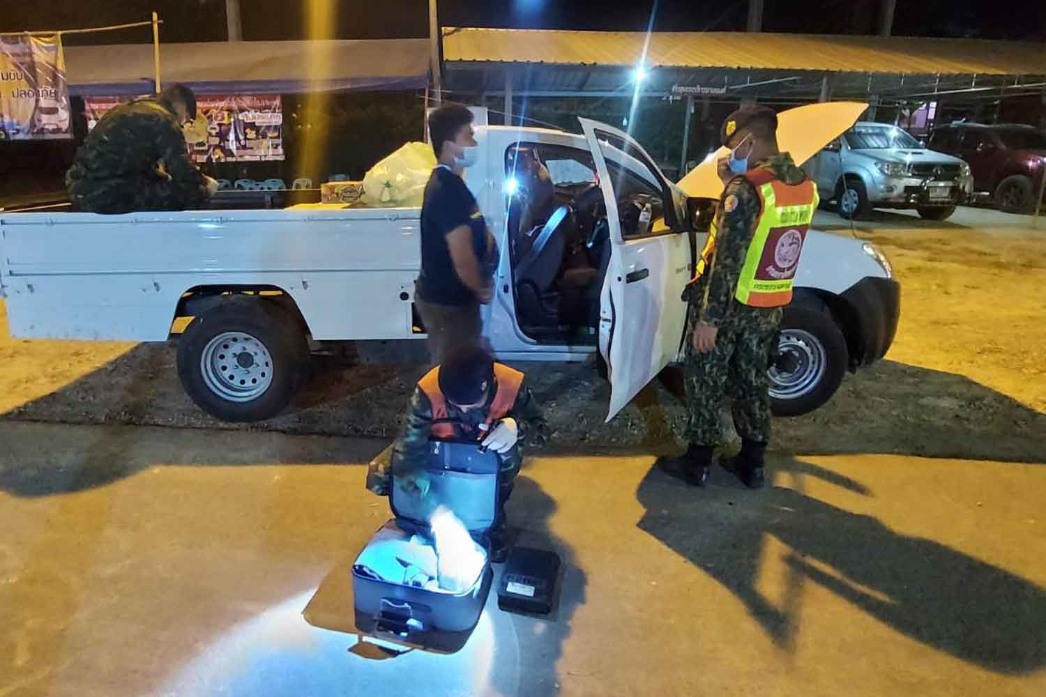 Police search a modified pickup at a checkpoint in Sangkhlaburi district, Kanchanaburi, on Tuesday night. Two Myanmar migrant workers travelling in it were arrested for breaking the travel ban. (Photo: Piyarat Chongcharoen)