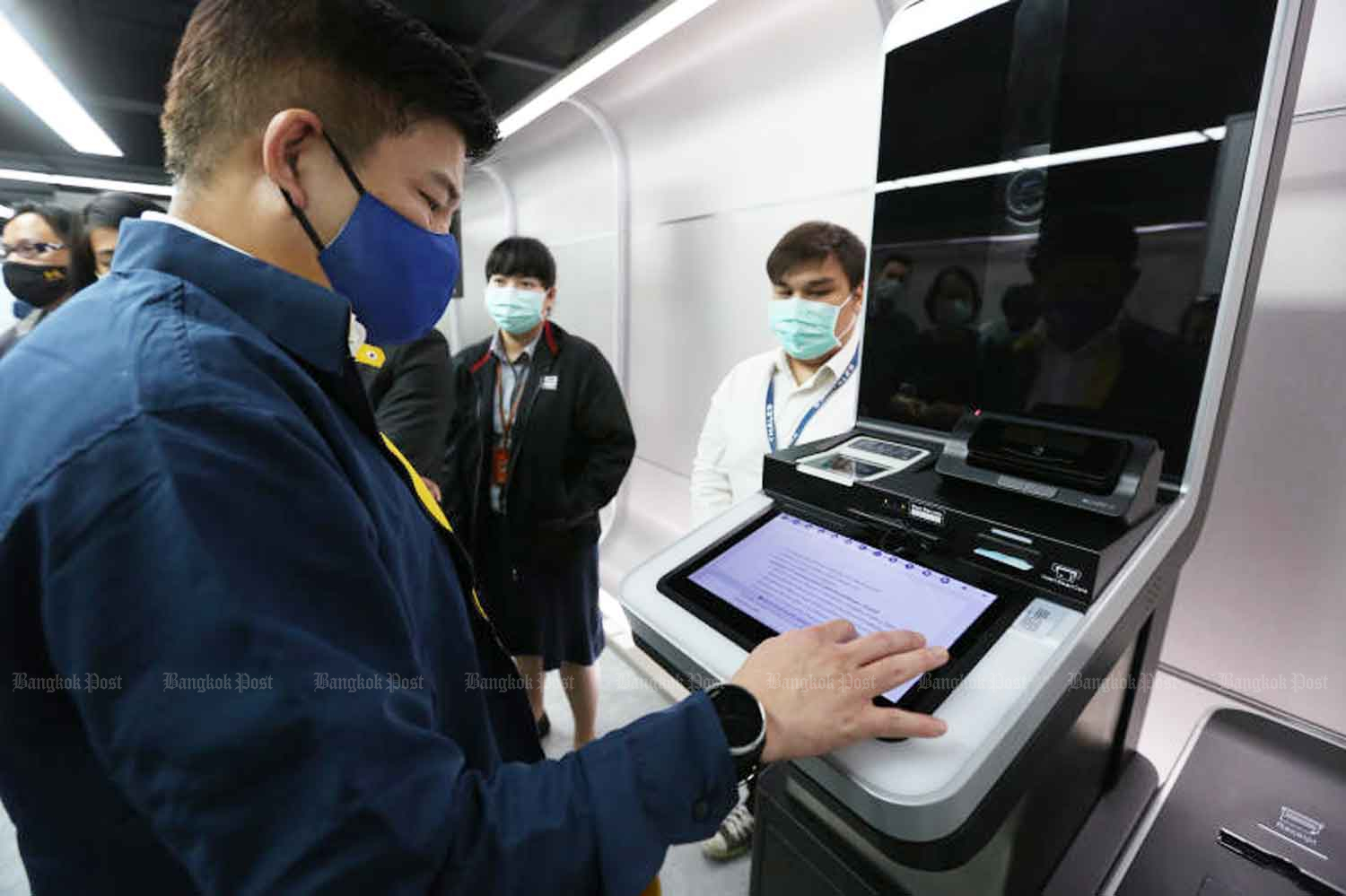 An officer demonstrates a digital information kiosk to visitors seeking consular services at the temporary passport office in Bangkok's MBK Centre. (Photo: Varuth Hirunyatheb)