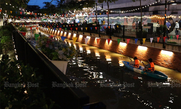 Tourists kayak along Bangkok's Ong Ang canal, which is decorated with colourful flags and lanterns to brighten the mood for residents. The weekend market nearby is reopened from Friday to Sunday from 3-8pm.
