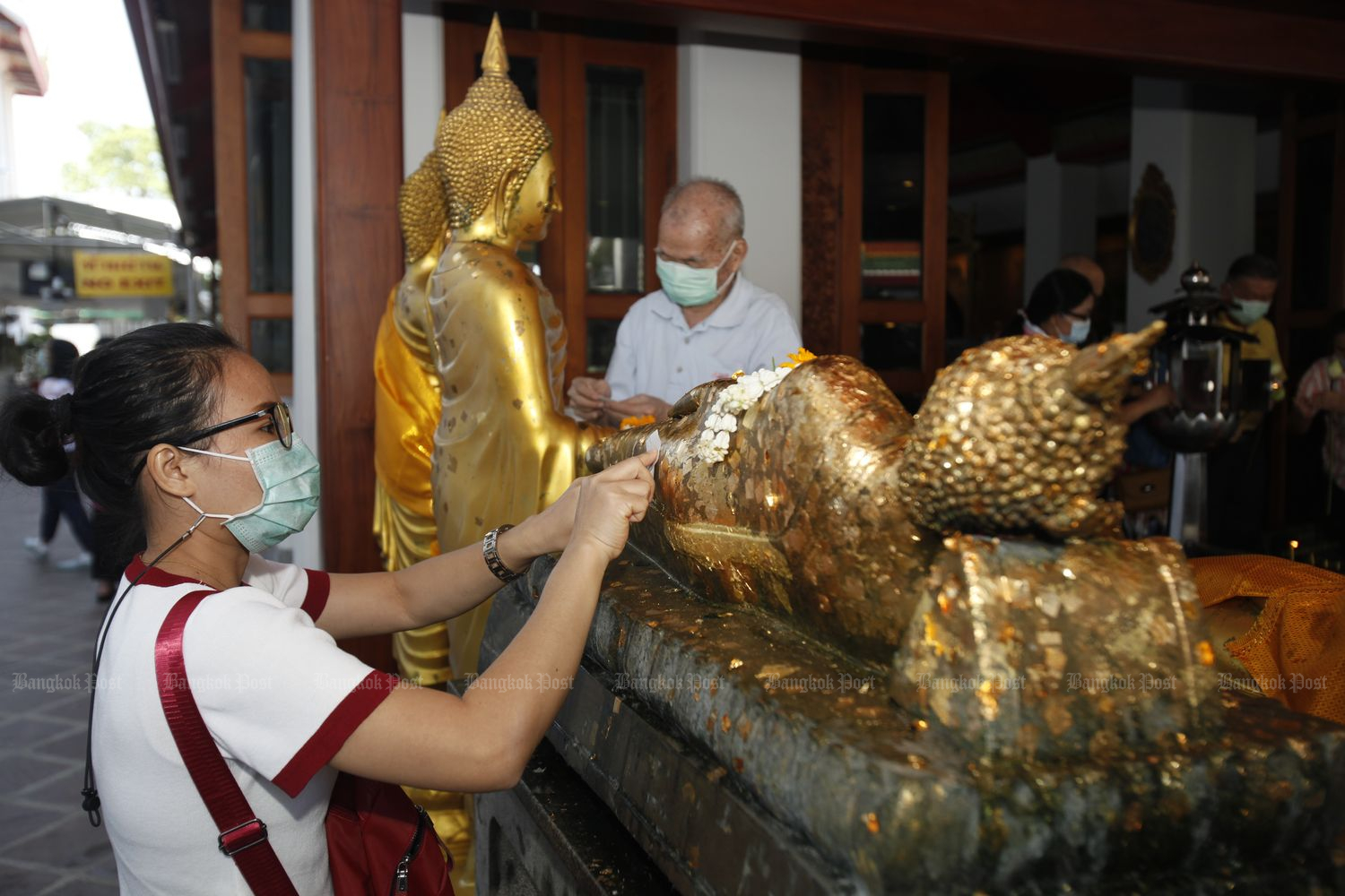 A woman places a golden leaf on a reclining Buddha image at Wat Phra Chetuphon Wimon Mangkhalaram (Wat Pho) in Bangkok on Friday. (Photo by Nutthawat Wicheanbut)