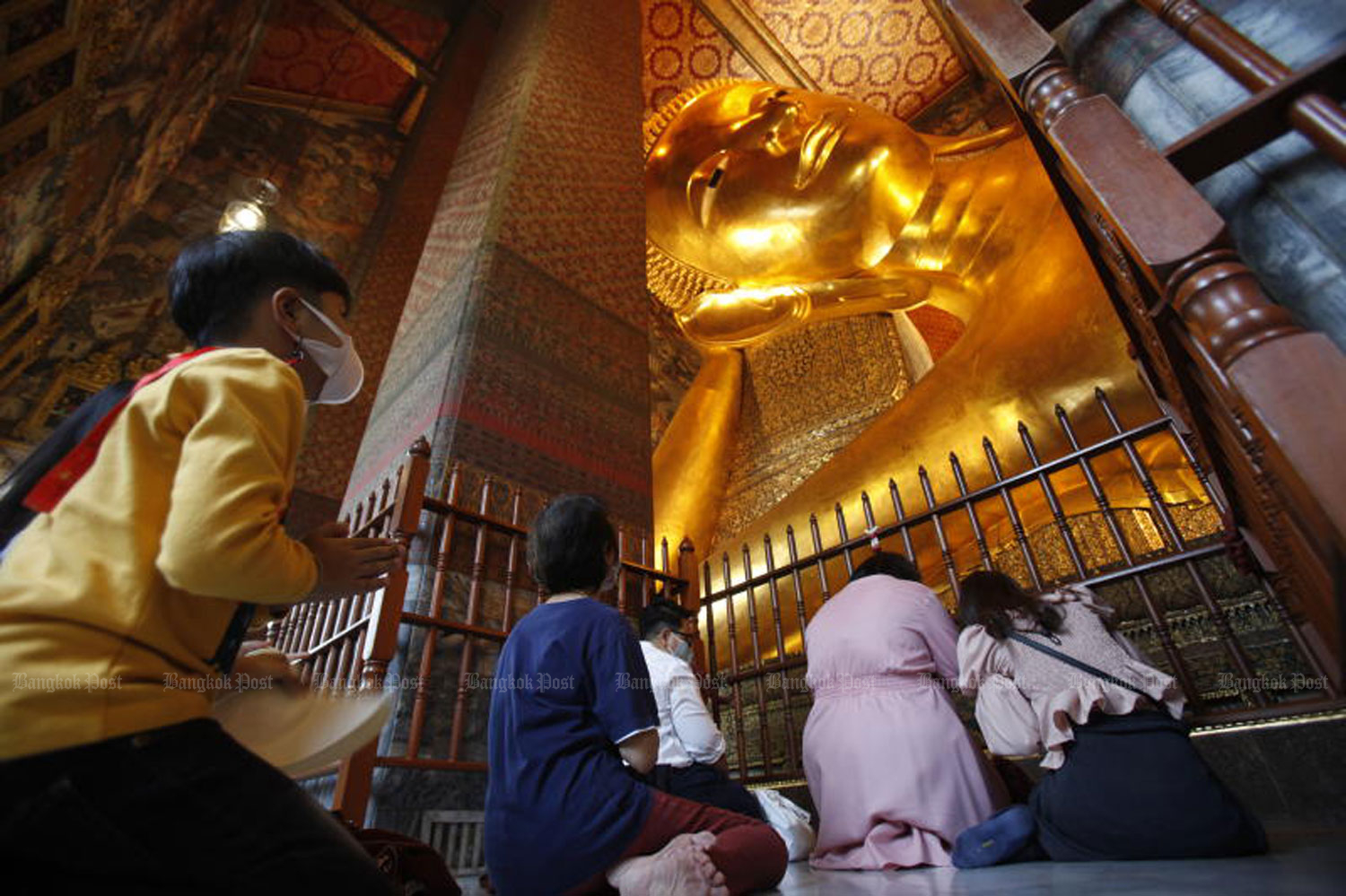 People pay homage to the giant reclining Buddha statue at Wat Phra Chetuphon Wimon Mangkhalaram (Wat Pho) in Bangkok on Friday. (Photo by Nutthawat Wicheanbut)