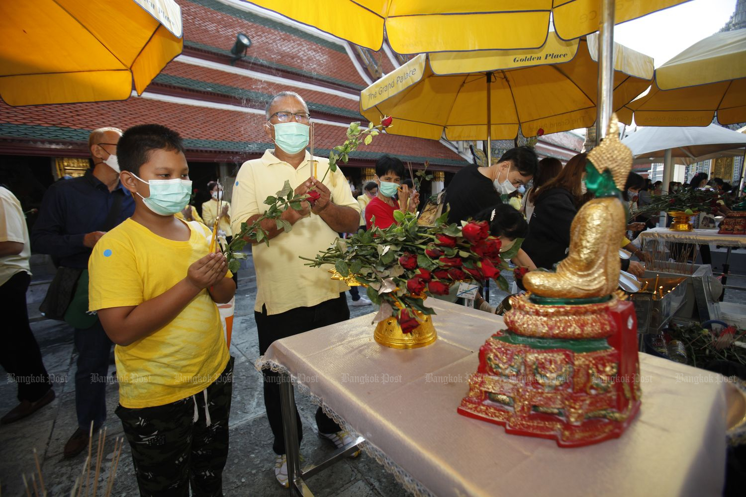 A man and a boy pay homage to the Emerald Buddha at Wat Phra Si Rattana Satsadaram (Wat Phra Kaeo) in Bangkok on the New Year occasion on Friday afternoon. (Photo by Nutthawat Wichieanbut)