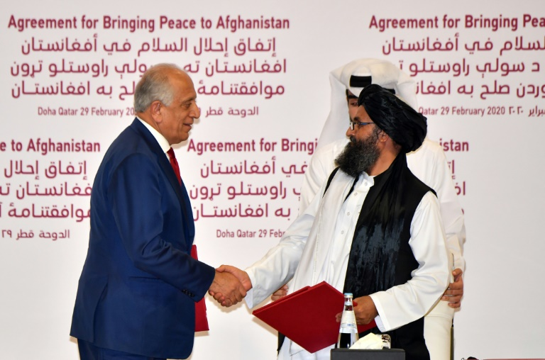 US Special Representative for Afghanistan Reconciliation, Zalmay Khalilzad, and Taliban co-founder Mullah Abdul Ghani Baradar shake hands after signing a peace agreement during a ceremony in the Qatari capital Doha.