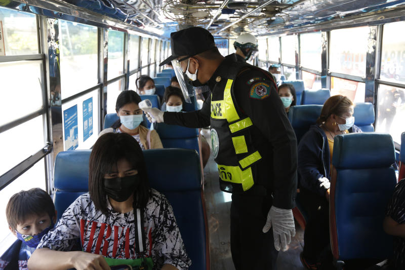 Bangkok Metropolitan Administration officials check the body temperatures of passengers on an interprovincial bus in Bang Na district for a Covid-19 test as the BMA strictly screens people entering the capital. (Photo by Wichan Charoenkiatpakul)